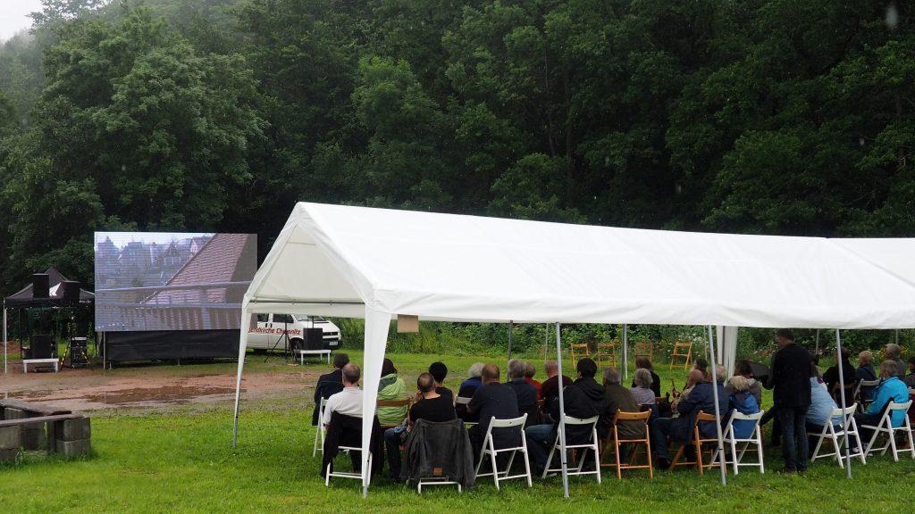 Besucher*innen mit Film im Hintergrund. Foto: sLAG